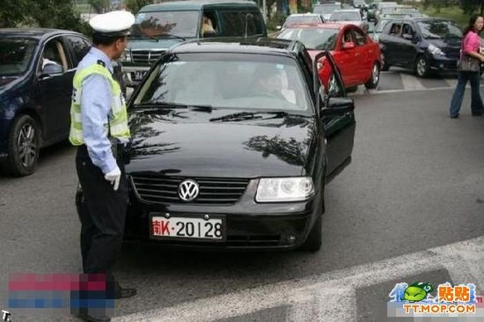 Китайский полицейский сдерживает толпу машин (12 фото)