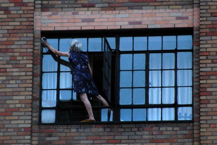 Бабуля-экстремалка моет окна (2 фото)