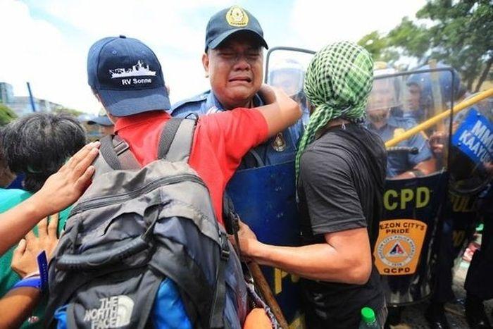 Протестующие люди поддержали расплакавшегося полицейского (4 фото)