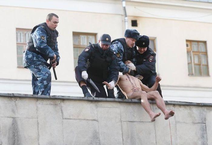 Петр Павленский на глазах у прохожих отрезал себе мочку уха (3 фото)
