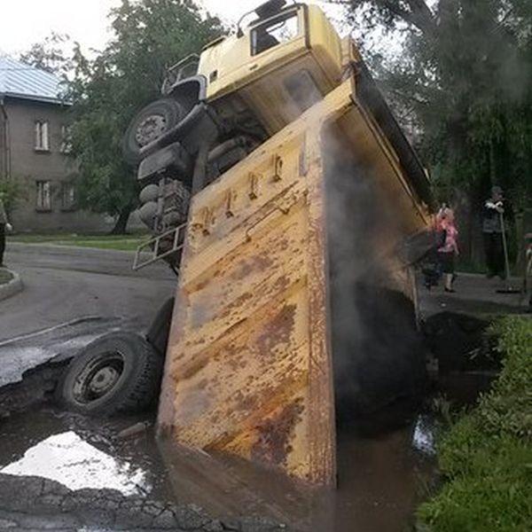 В Санкт-Петербурге грузовик с асфальтом провалился в огромную яму на дороге (3 фото)