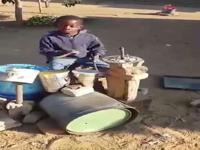 Темнокожий мальчуган играет на самодельных барабанах