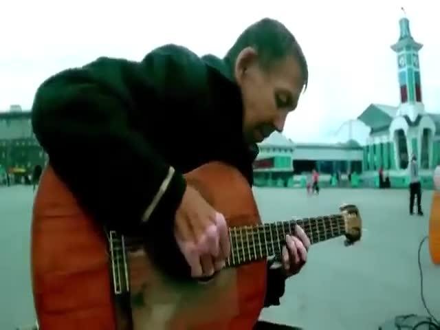 Бездомный мужчина играет на гитаре