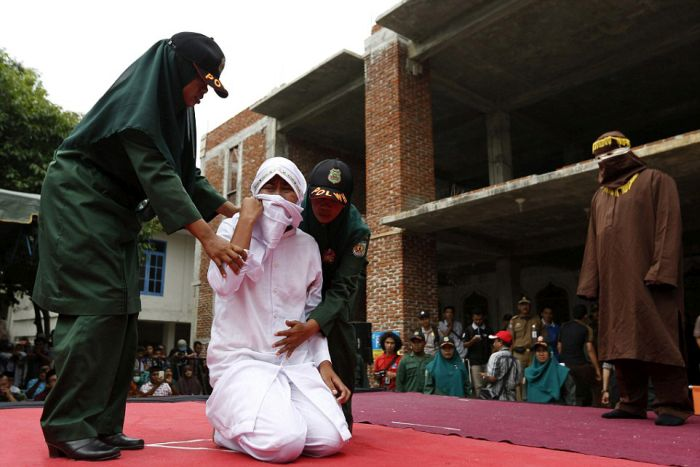В Индонезии девушку публично наказали за секс вне брака (4 фото)
