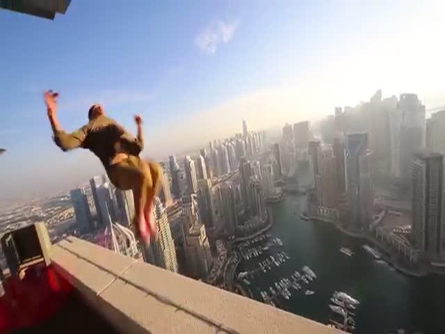 Экстремал Олег Шерстяченко выполняет опасные трюки на крыше небоскреба