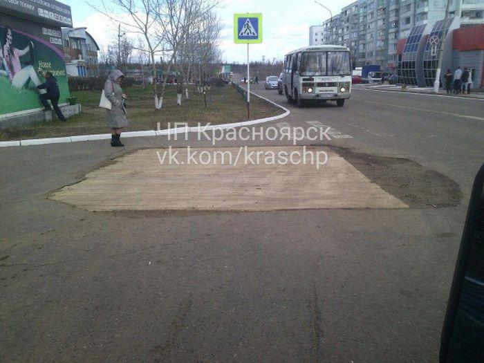 В Красноярском крае яму на дороге прикрыли деревянным помостом (2 фото)