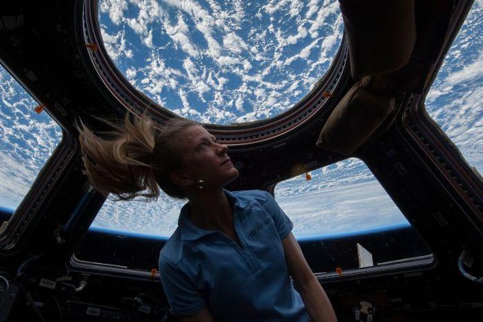 Скол на стекле иллюминатора МКС на фоне черного космоса (2 фото)