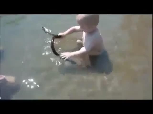 Маленький мальчик играет со змеей