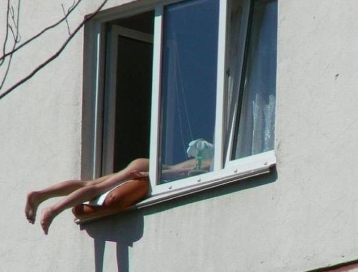 Жители Новосибирска жалуются на женщину, загорающую обнаженной на подоконнике своей квартиры (3 фото)