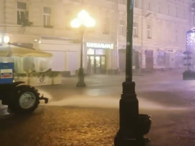 Трактор моет улицы Москвы во время дождя