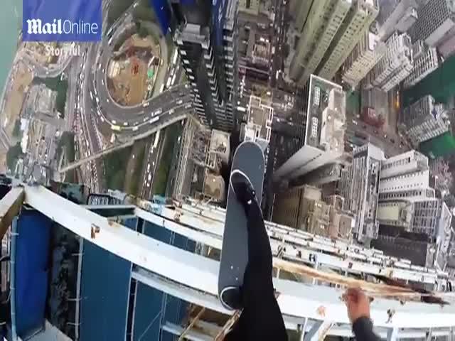 Парень балансирует на скейтборде на крыше небоскреба