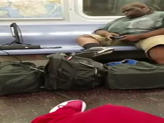 Пассажир нью-йоркского метро играет в приставку