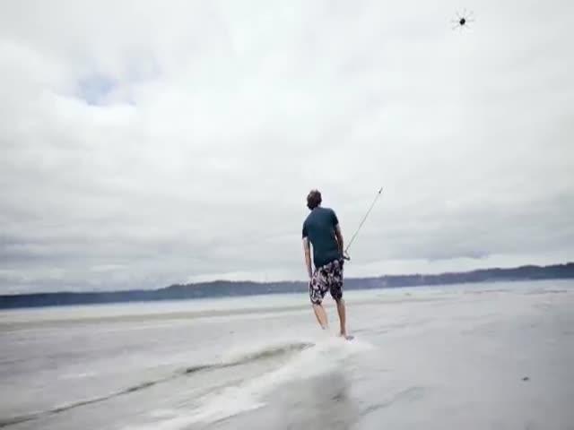 Серфер катается на волнах с помощью дрона