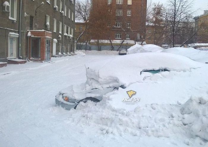 В Новосибирске грузовик проехал по капоту скрытой под сугробом машины (2 фото)