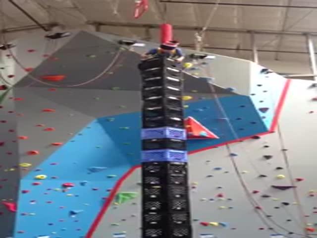 Юный альпинист на башне из ящиков