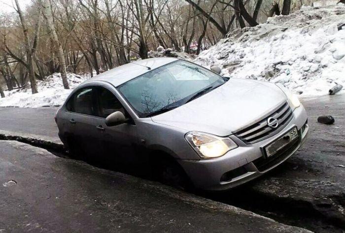 В Омске машины проваливаются в ледяные трещины на дорогах (3 фото)