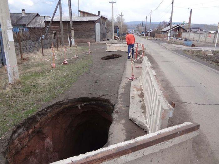 «КамАЗ», приехавший засыпать яму на дороге, провалился в нее (2 фото)