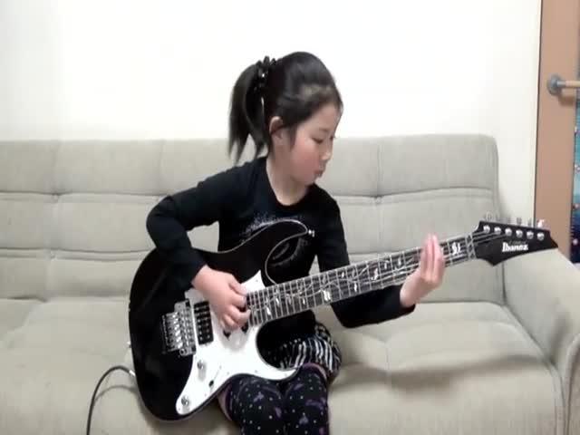 8-летняя девочка играет на электрогитаре
