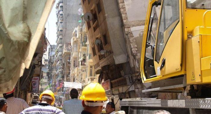 Упавшая многоэтажка уперлась в соседний дом (6 фото)