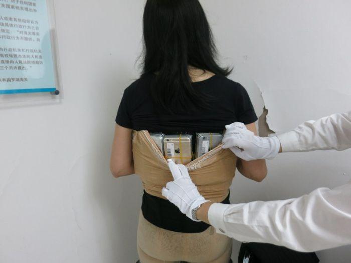 Девушка пыталась перевезти смартфоны и элитные часы, примотав их к телу (4 фото)