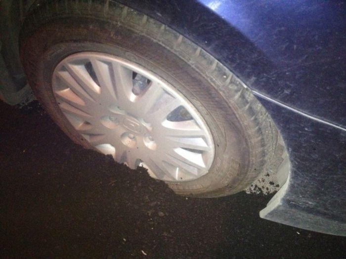 В Екатеринбурге дорожники заасфальтировали колесо припаркованной машины (2 фото)