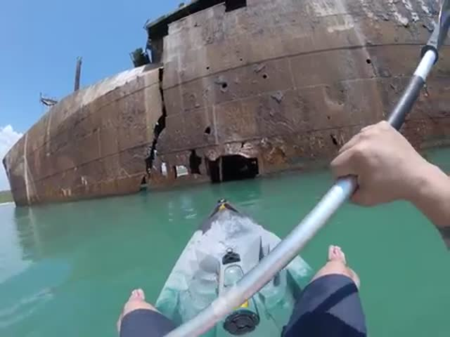 Каякер исследует севшее на мель судно