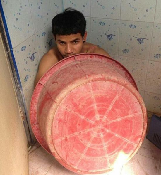 В Таиланде преступник пытался спрятаться от полиции под тазиком (4 фото)