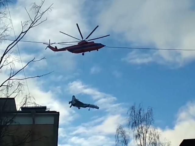 Очевидцы в Питере сняли на камеру вертолёт Ми-26 с истребителем на подвесе