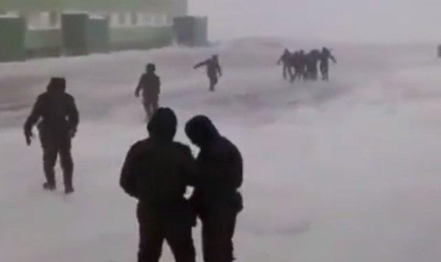 Солдаты пытаются пройти к зданию сквозь порывы сильнейшего ветра