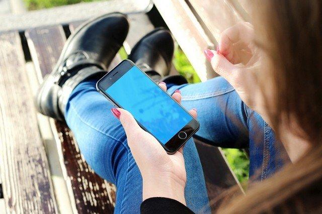 Девушка держит смартфон в левой руке. Она одета в джинсы и синие ботнки, а на руках у нее красный маникюр