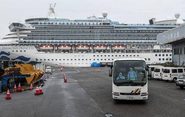 Корабль Diamond Princess стоит у причала, а от него отъезжает автобус, за рулем которого люди в защитных костюмах от коронавируса