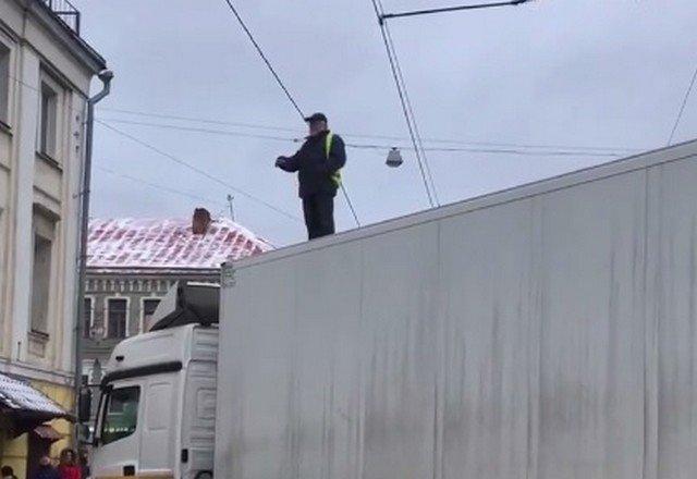Виктор Синебрюхов стоит на крыше белой фуры в центре Москвы