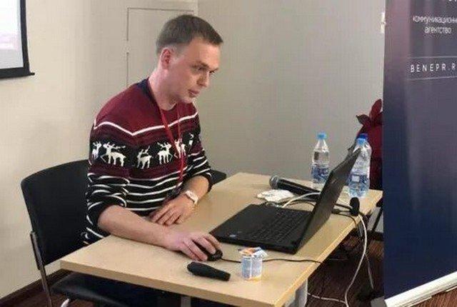 Иван Голунов сидит в свитере с оленями за столом,на котором стоит ноутбук и вода