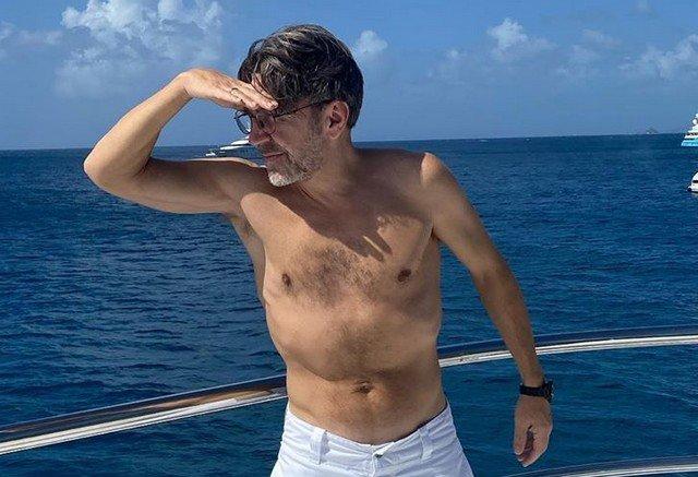 Сергей Шнуров стоит на яхте и прикрывает правой рукой лицо от солнца