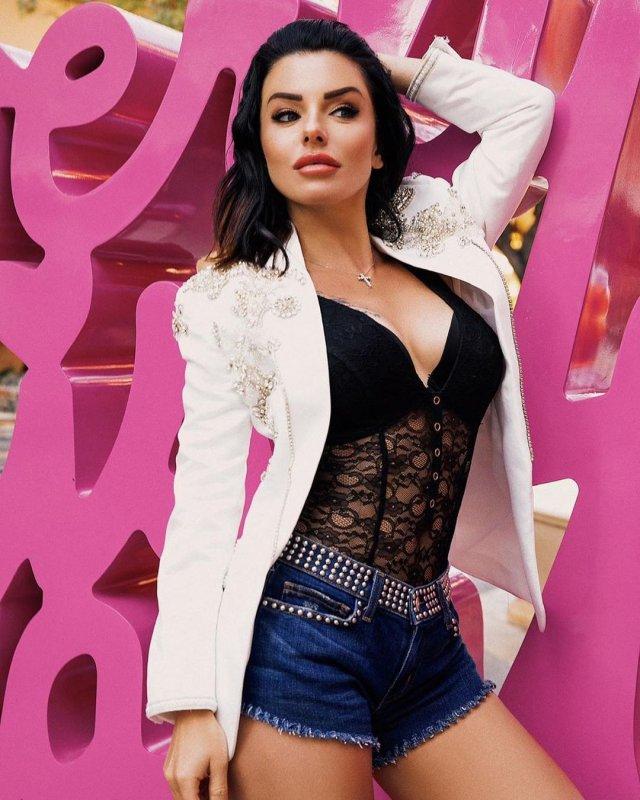 Юлия Волкова в белой куртке, черной кофте и джинсовых шортах на фоне  розовых надписей
