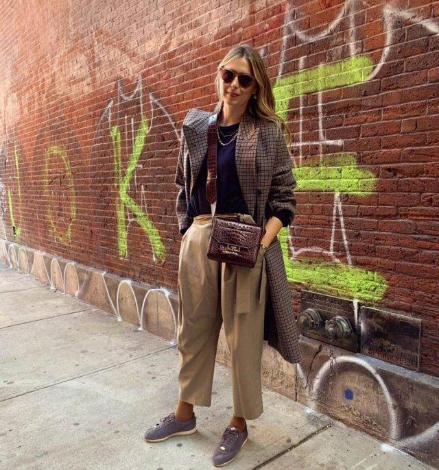 Мария Шарапова в коричневом костюме на фоне кирпичной стены