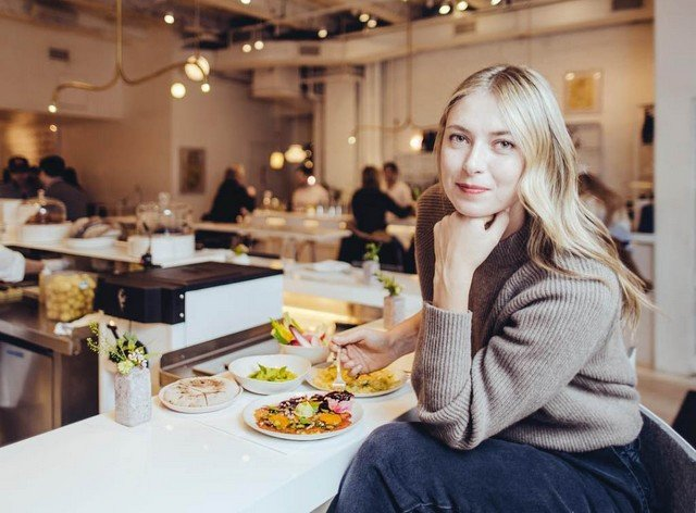 Мария Шарапова в коричневом свитере за столом,где много еды