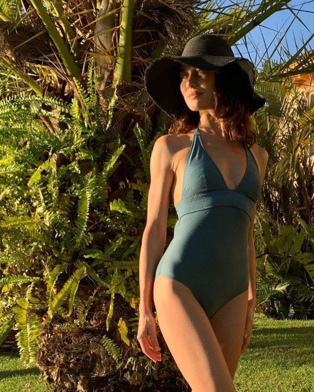 Ольга Куриленко в синем купальнике около пальмы