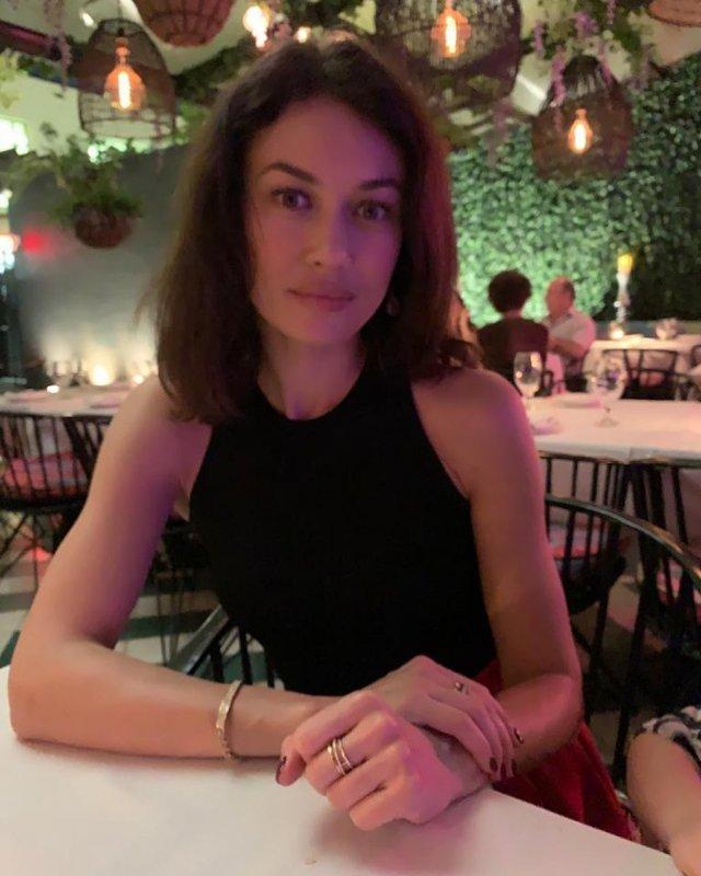 Ольга Куриленко в черной кофте и ювелирных украшениях на руках в ресторане