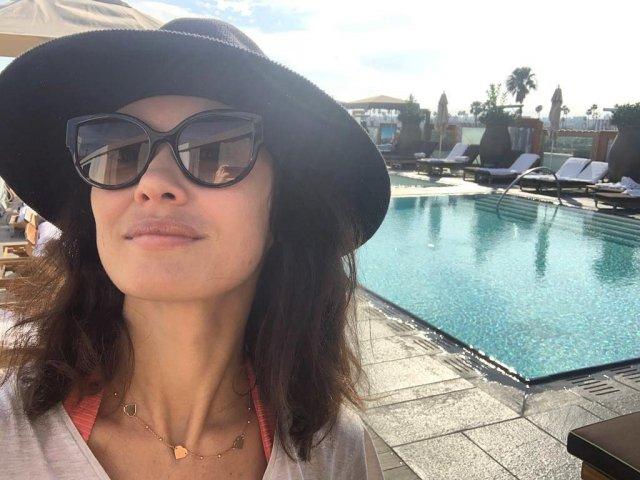 Ольга Куриленко в черных очках и шляпе около бассейна