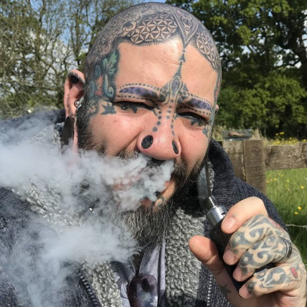 Пол Мэтью с татуировками и пирсингом