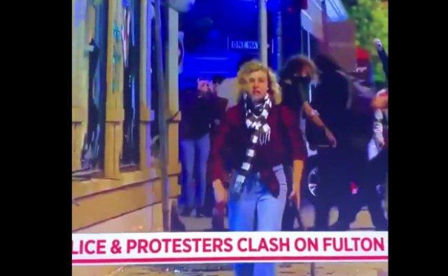 На протестах в США заметили странную девушку, пытавшуюся разбить бронированное стекло