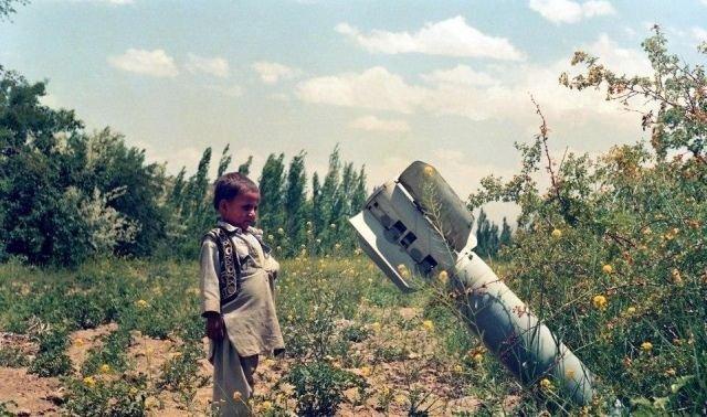 Афганский мальчик смотрит на неразорвавшеюся бомбу