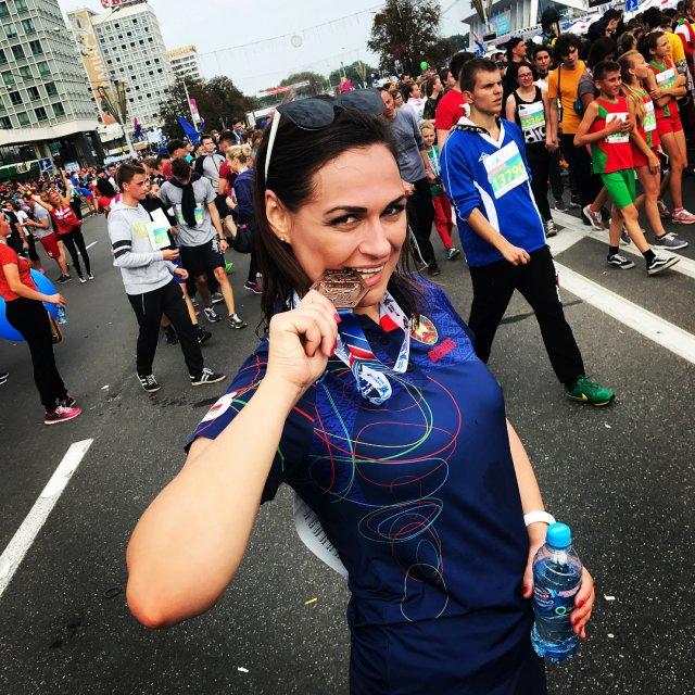 Наталья Эйсмонт с медалью во рту после пробега