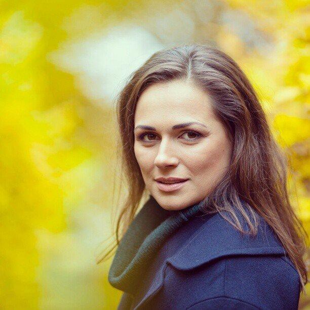 Наталья Эйсмеонт в синем костюме на фоне осенней листвы