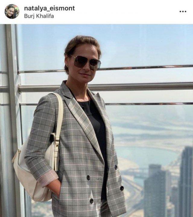 Наталья Эйсмонт в небоскребе в пиджаке в серую клетку и белой сумкой