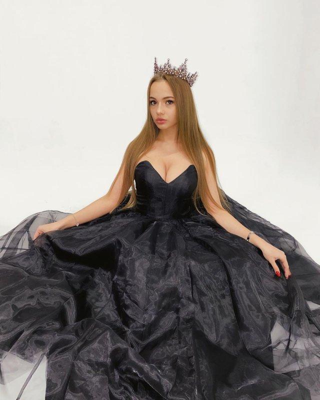 Валя karna.val в черном платье и короне на фоне белой стены