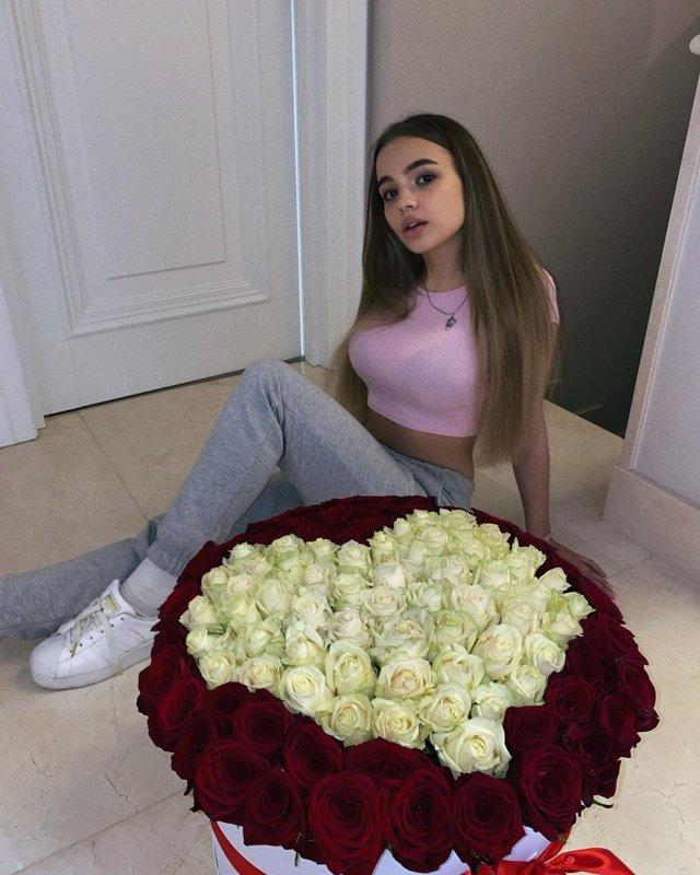 Валя karna.val на полу в серых штанах и розовой кофте с розами в виде сердца