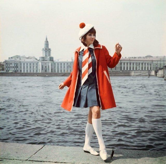 Девушка на набережной в Петербурге в красном пальто, синем платье и галстуке в полоску