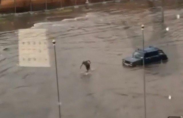 Мужчина тащит машину на тросе по колено в воде